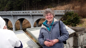 Judy braving the heavy drizzle sans hood at Rocky Creek Bridge.
