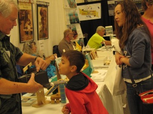 Gary Hartman shows a young man a homemade kaleidoscope that is one of the projects from his book Kids' Book of Adventure Projects.