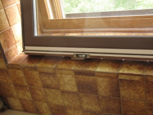 In this close up, notice the latch resting on the sill, indicated that the window is tilted upside down.
