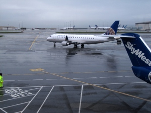 Plane on tarmac in SFO in rain. Weather causes delay problems here regularly.